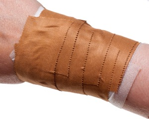 A wrist taped with tan-coloured zinc oxide tape